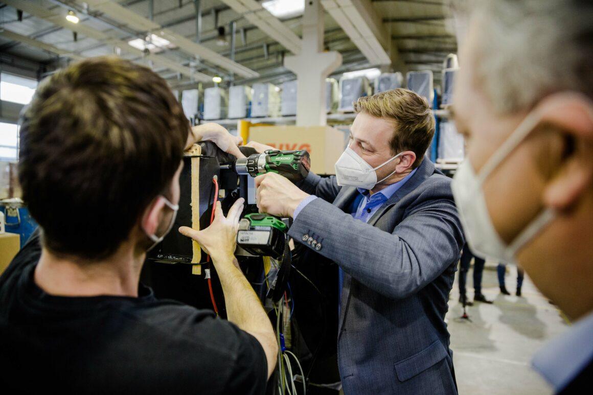Landesrat Stefan Kaineder mit Akkuschrauber bei Firma Guntamatic